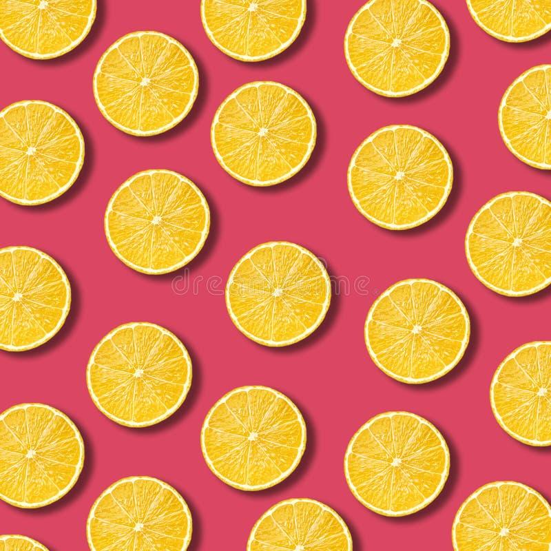 Lemon slices pattern on vibrant pomegranate color background royalty free stock photography