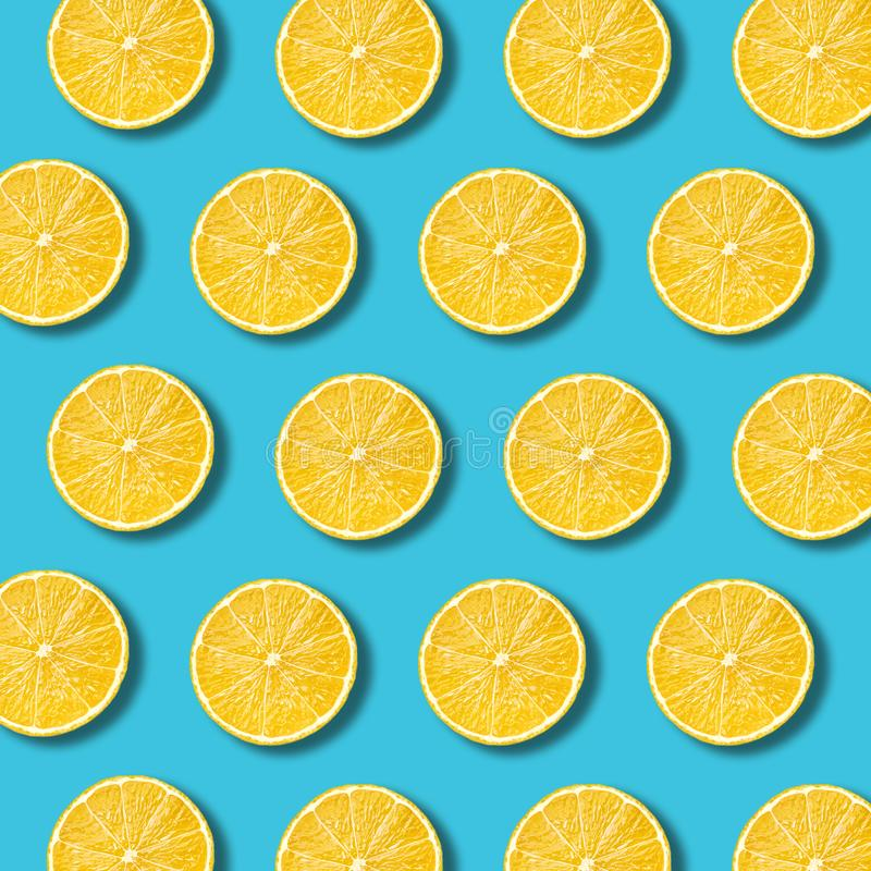 Lemon slices pattern on vibrant turquoise color background. Minimal flat lay food texture royalty free stock photography