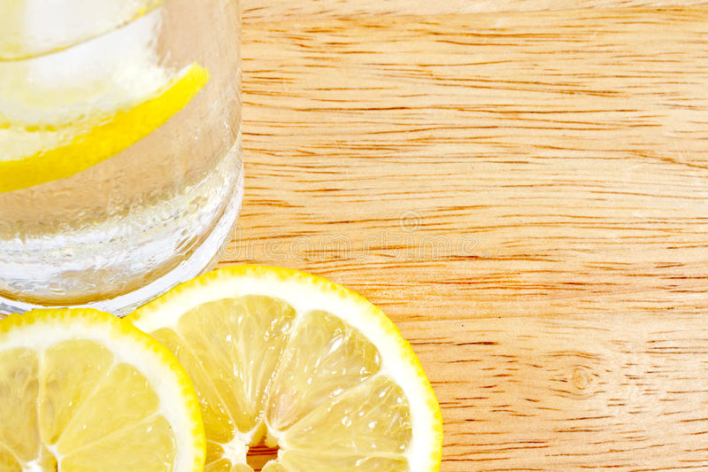 Lemon slices on wood with glass royalty free stock images