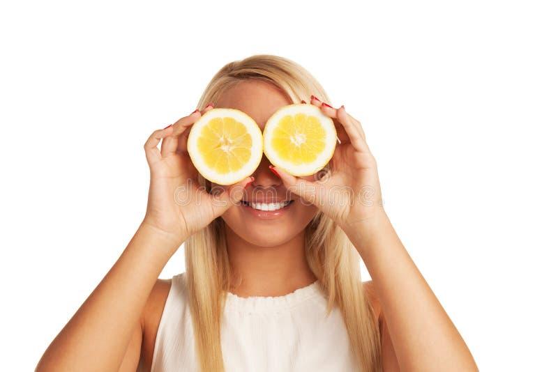 Lemon smile. Girl playing with lemon on isolated white background stock photo