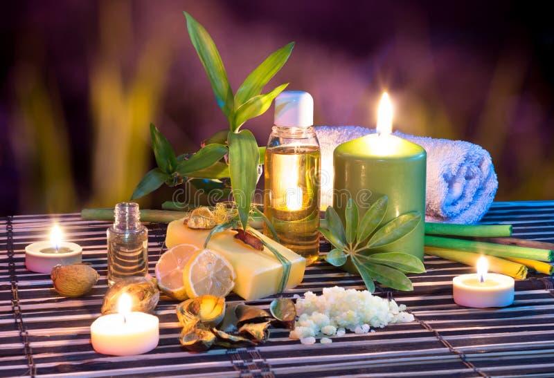 Lemon soap , oil, towel, salt, bamboo, and candles in garden. Aromatherapy -lemon soap , oil, towel, salt, bamboo, and candles in garden stock image