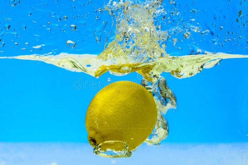 Lemon splashed in water. space for text. light blue background. clear water. stock image