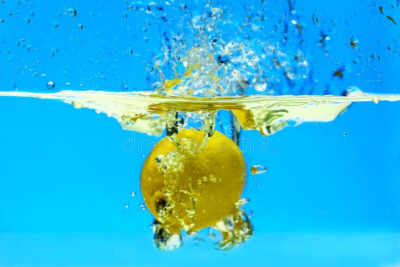 Lemon splashed in water. space for text. light blue background. clear water. stock photography