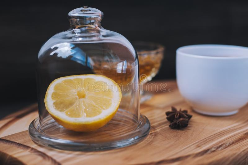 Lemon, star anise, honey and tea on stand. Green tea in white cup, lemon under transparent lid. Morning tradition stock image
