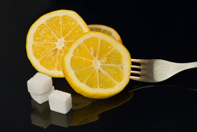 Lemon and sugar. Lemon, sugar and fork isolated on black stock image