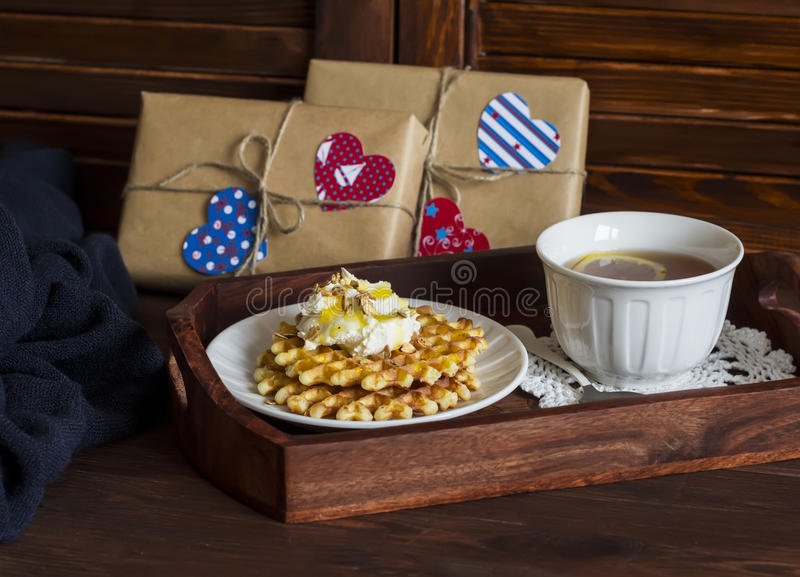 Lemon tea, waffles with ice cream, honey and nuts in a vintage tray, homemade Valentine's day gifts in kraft paper. On a brown wooden table stock photos