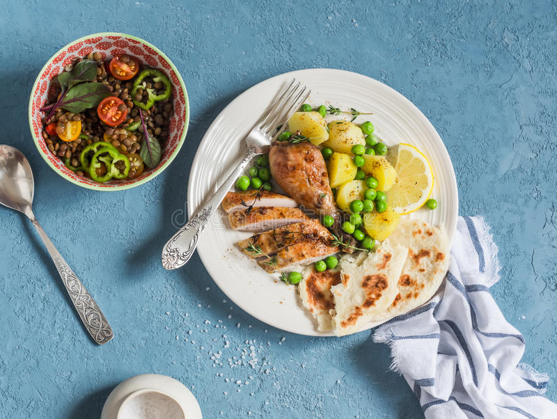 Lemon thyme baked chicken, boiled potatoes with green peas, salad with lentils and tomatoes on a blue background. stock image