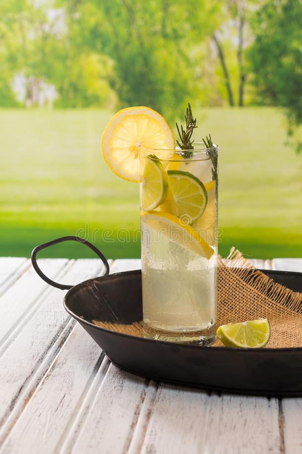 Lemon water drink in glass sitting on a black tray with burlap n royalty free stock images