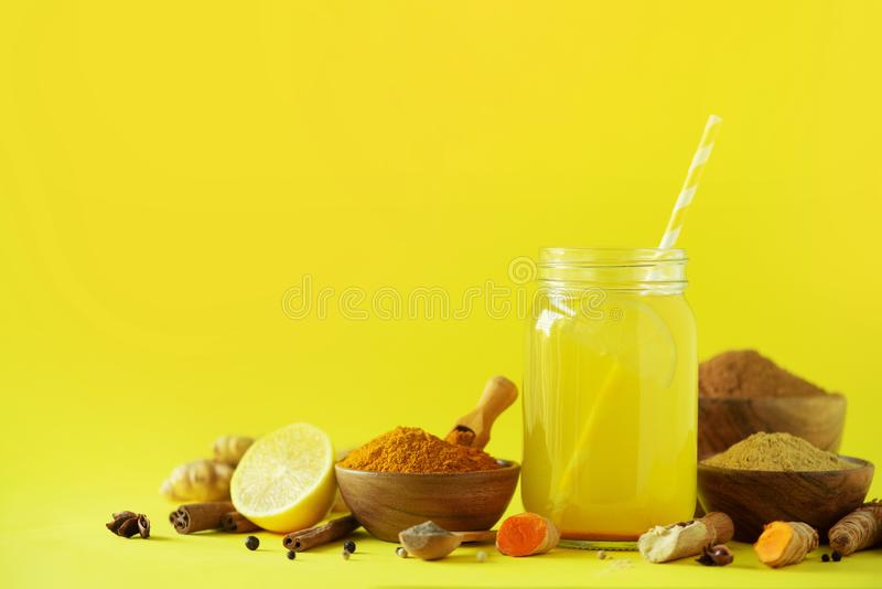 Lemon water with ginger, curcuma, black pepper. Vegan hot drink concept. Ingredients for orange turmeric drink on btight yellow stock photo