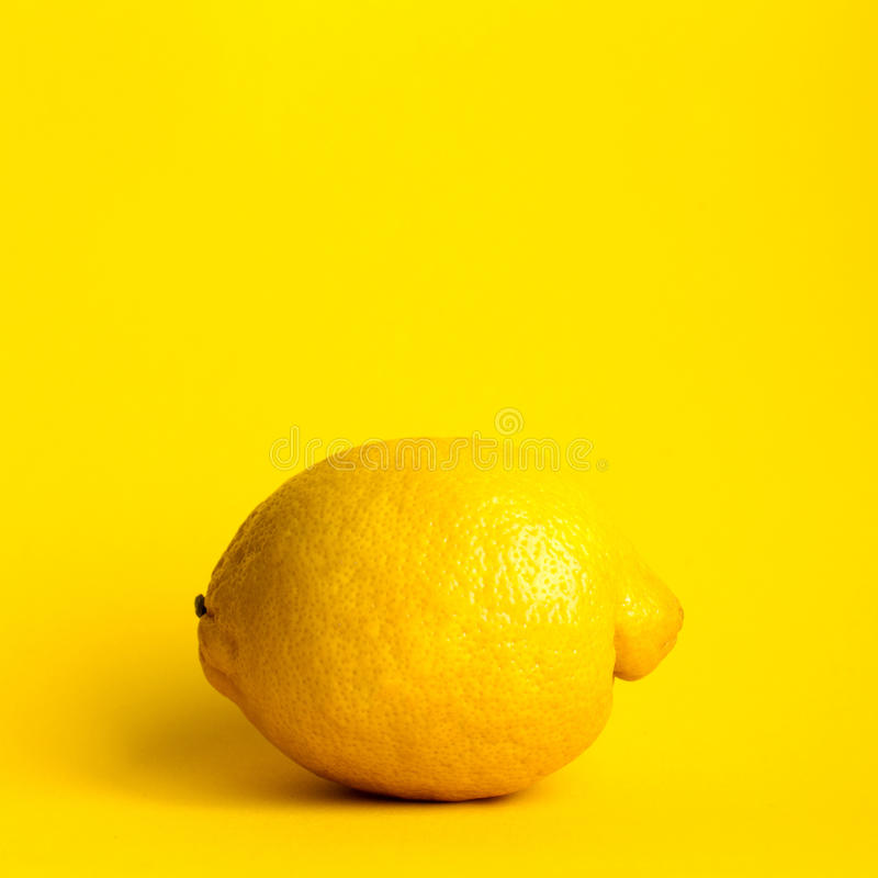 Lemon on yellow background royalty free stock photography