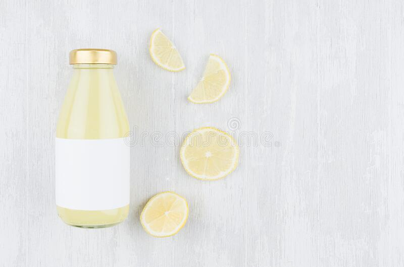 Lemon yellow juice in glass bottle with blank label, sliced fruit on white wood board, top view, copy space, mock up for design. Lemon yellow juice in glass stock photography