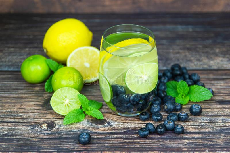 Lemon and Yellow lemon with blueberry in glass on wood table for hot summer days. And good for health royalty free stock photography