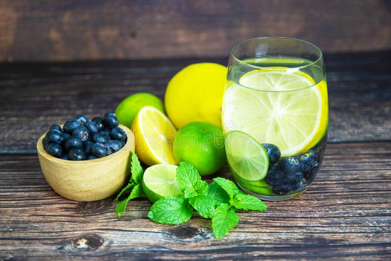 Lemon and Yellow lemon with blueberry in glass on wood table for hot summer days. And good for health stock photography
