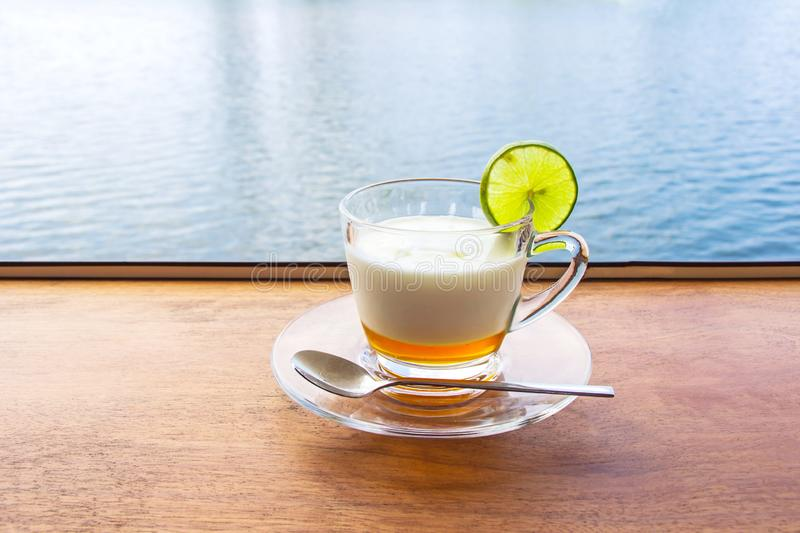 Lemon yogurt fresh milk in a clear glass placed on a brown wooden table with sea water surface background stock image