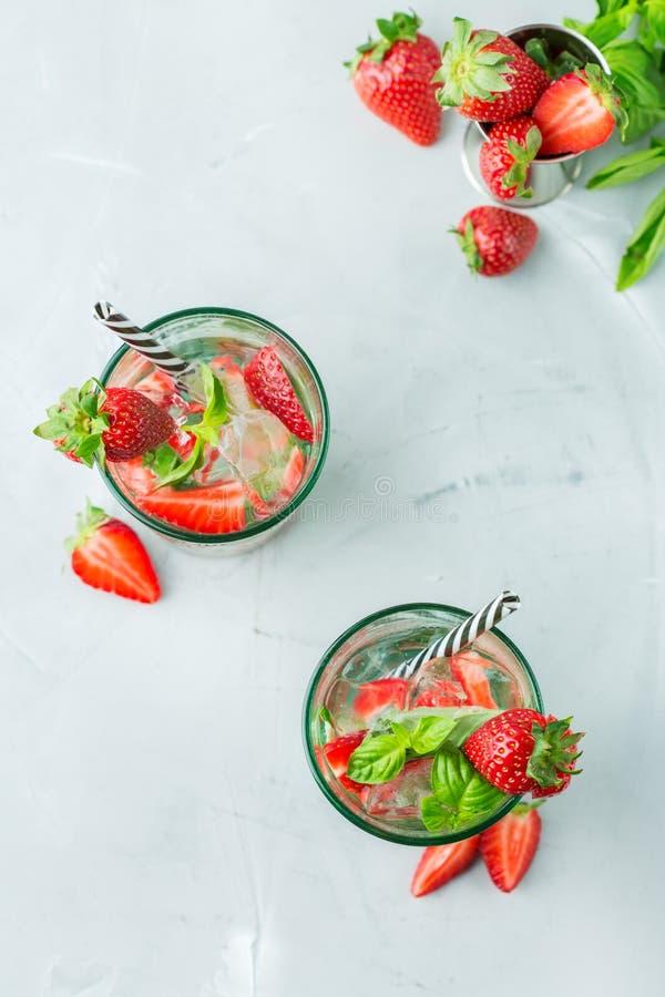 Lemonad för alkoholcoctailmojito med rom, sodavatten, jordgubben och basilika fotografering för bildbyråer