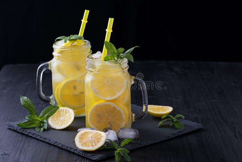 Lemonad i en krus med is och mintkaramellen på en svart trätabell royaltyfria bilder