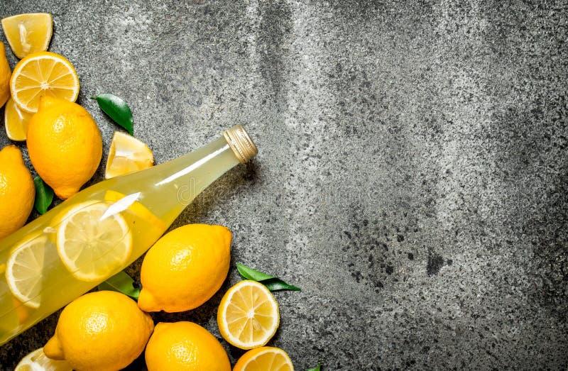 Lemonad i flaskan med skivor av nya citroner royaltyfria foton