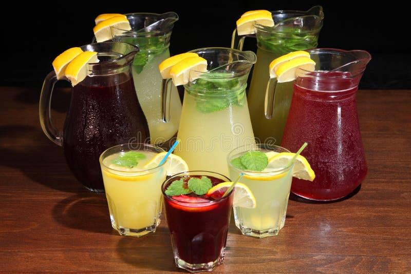 Lemonad i tillbringaren och citronerna med mintkaramellen på tabellen inomhus Rosa lemonad med citronen, limefrukt och jordgubbar royaltyfria foton