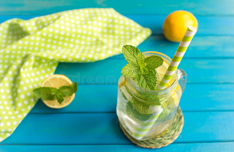 Lemonad with lemon slices and mint in a jar mug with straw. On blue wooden background from top view. Water with lemon. Detox royalty free stock images