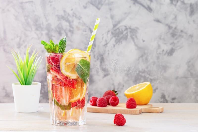Lemonad med bär och mintkaramellen Bredvid skärbrädan är ingredienserna Förnyande drink för sommar i ett högväxt exponeringsglas royaltyfria bilder