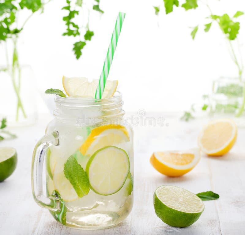 Lemonad med is-, citron- och limefruktskivor i kruset, sugrör arkivbild
