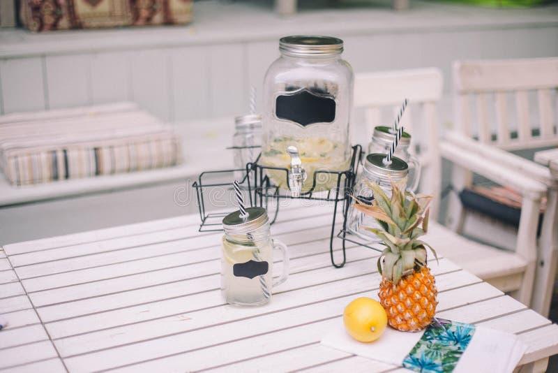 Lemonad med citron-p?ron lemonad N?rliggande ?r en dekor med en flaska, en citron och en ananas fotografering för bildbyråer