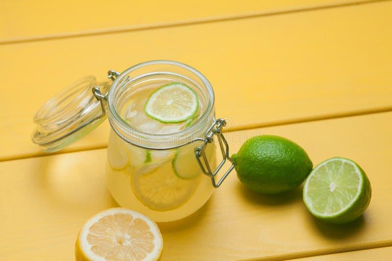 Lemonad med is, citronen och limefrukt i en krus på gula trälodisar royaltyfria bilder