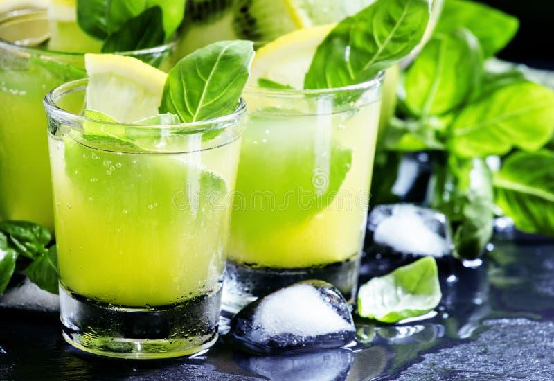Lemonad med kiwin, grön basilika, grapefruktsirap och is, svart arkivbild
