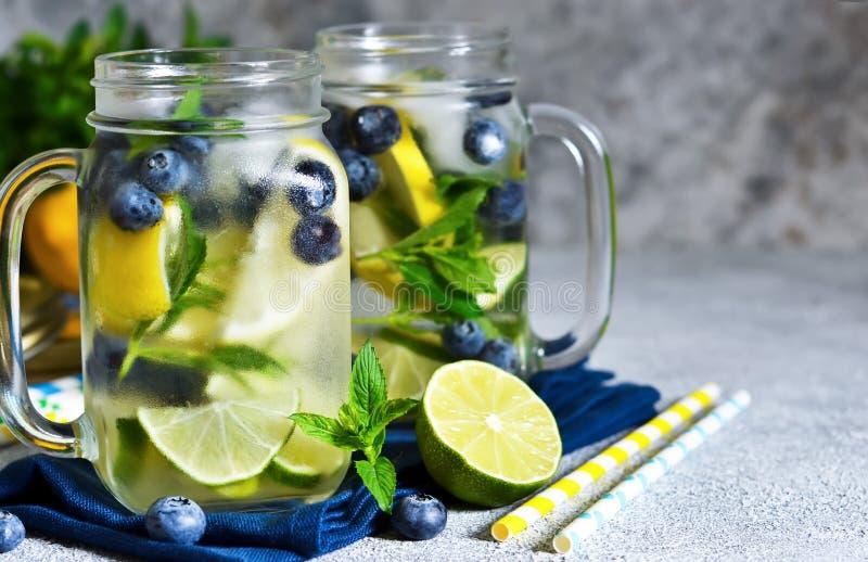 Lemonad med limefrukt, citronen och bl?b?r p? en stenbakgrund royaltyfri foto