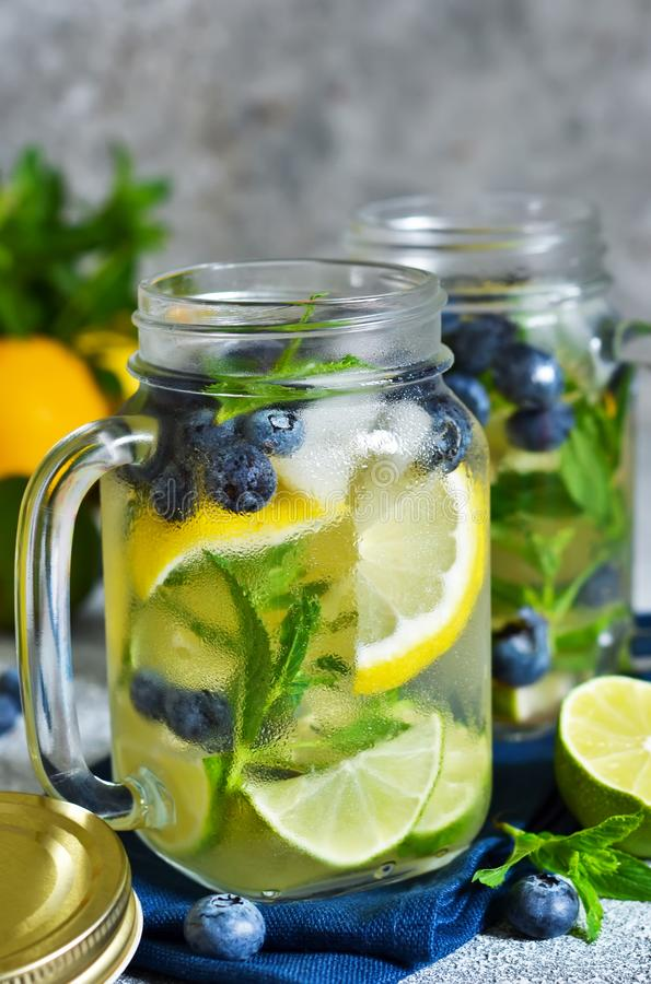 Lemonad med limefrukt, citronen och bl?b?r p? en stenbakgrund royaltyfri fotografi