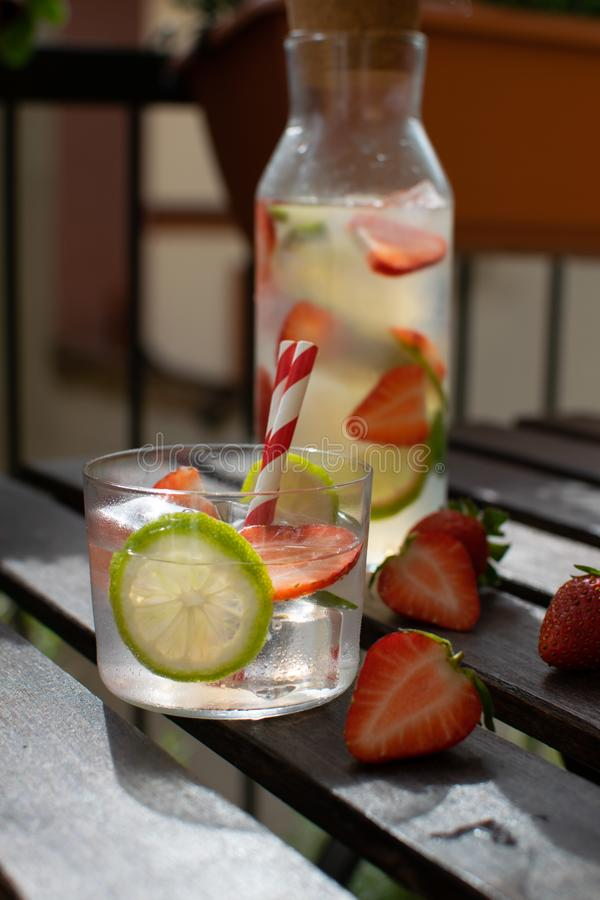 Lemonad med limefrukt och jordgubben på en balkongnolla-terrass, papperssugrör, plast- fri restaurang royaltyfri foto