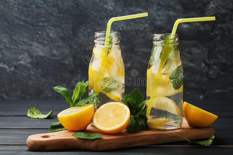 Lemonaddrink av den sodavattenvatten, citronen och mintkaramellen i krus på svart bakgrund arkivbilder