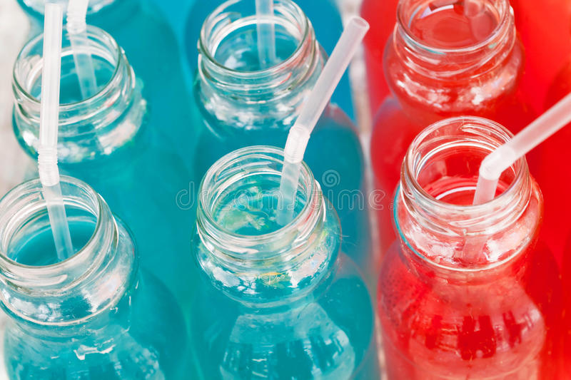 Lemonade from berries and syrup, red and blue colors on the table royalty free stock photos