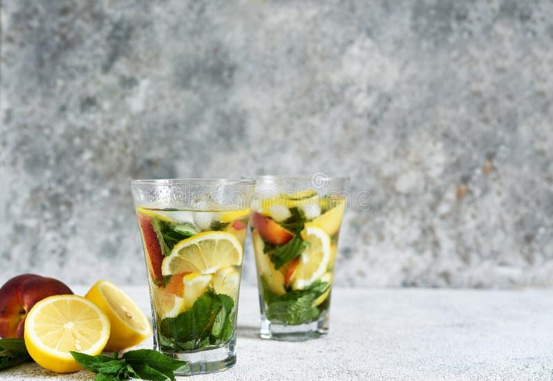 Lemonade con pesche e menta in una tazza di vetro su fondo di calcestruzzo Limonata di pesche fotografie stock