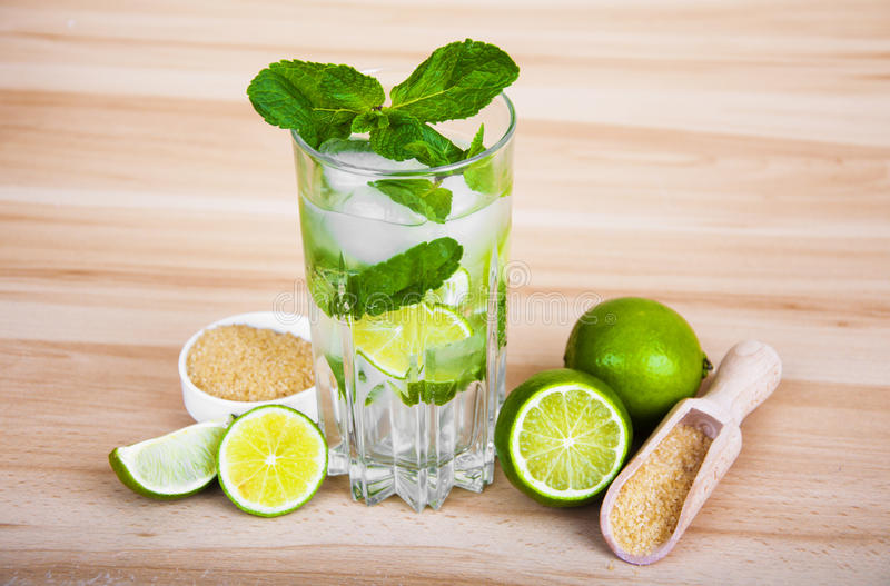 Lemonade. Fresh limes and mint on wooden background stock images