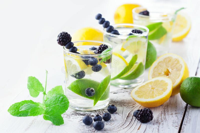 Lemonade in a glass with mint. Fresh summer lemonade with mint and berries on a white wooden background, selective focus stock images