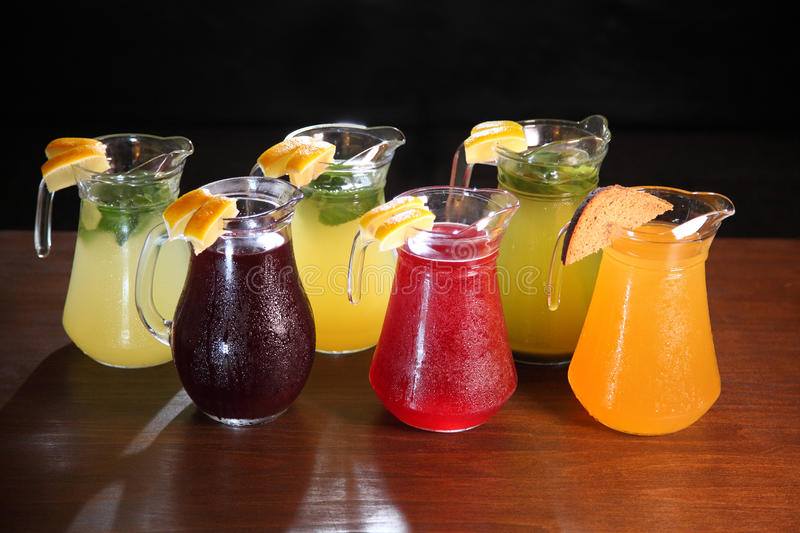 Lemonade in the jug and lemons with mint on the table indoor. Quenching thirst and refreshing drinks. Cold lemonades. Lemonade. Morse. Compote stock photography