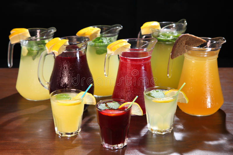 Lemonade in the jug and lemons with mint on the table indoor. Quenching thirst and refreshing drinks. Cold lemonades. Lemonade. Morse. Compote stock images