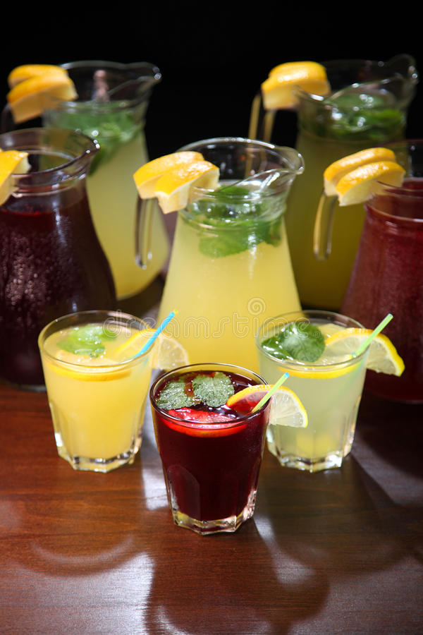 Lemonade in the jug and lemons with mint on the table indoor. Quenching thirst and refreshing drinks. Cold lemonades. Lemonade. Morse. Compote royalty free stock photography