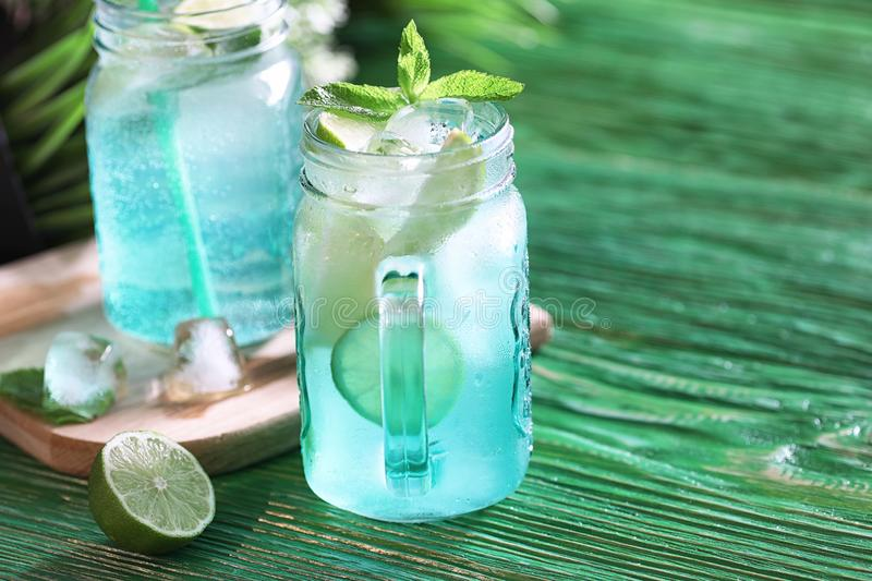 Lemonade from lime and mint. In a glass jar on a tabler stock photo