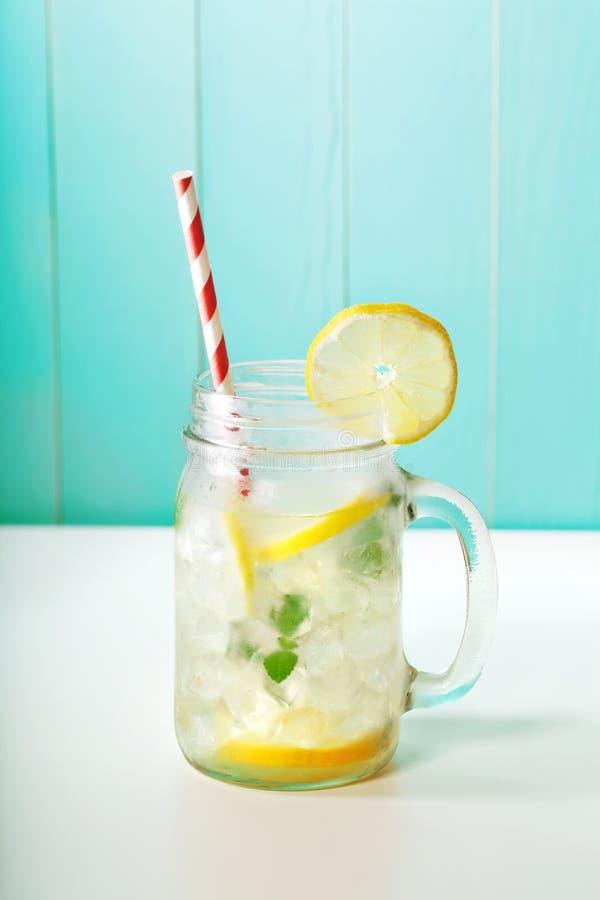 Lemonade in mason jar. Homemade lemonade in a mason jar with big red striped straw royalty free stock photo