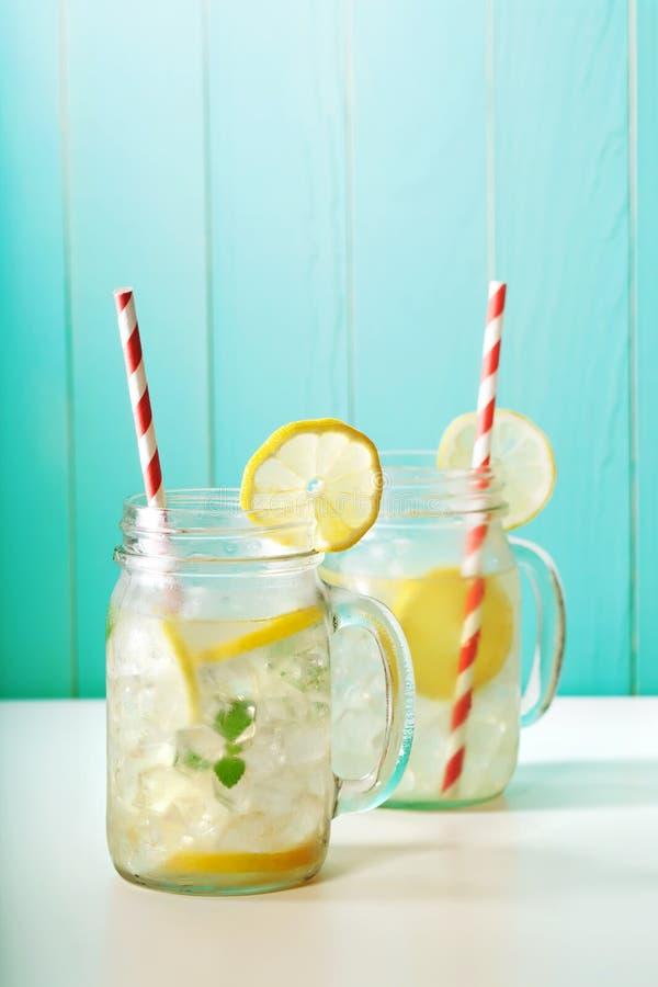 Lemonade in mason jars. Homemade lemonade in mason jars with big red striped straws royalty free stock images