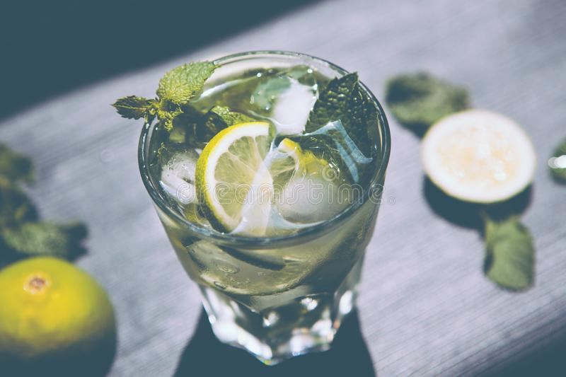 Lemonade or Mojito coctail with lime, mint and ice, fresh drink. In vintage colors stock image