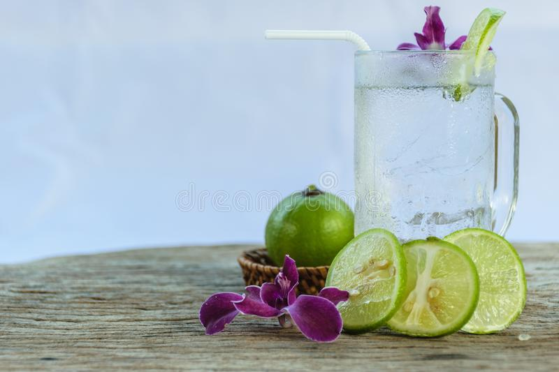 Lemonade refreshing. And pieces of lemon put on clear white glass for drinking,old wooden background and purple orchids put in side of it stock image