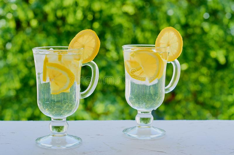 Lemonade water in the glasses on the blurred nature background. Cocktail with fresh lemon juice and ice. Healthy drinks stock photo