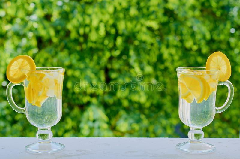 Lemonade water in the glasses on the blurred nature background with copy space on the centre. Summer cold cocktails with lemons stock image