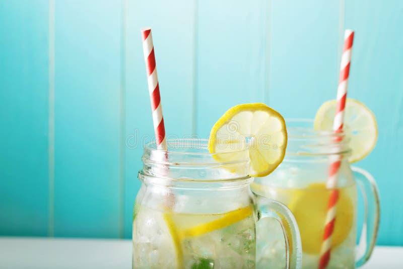 Lemonades in mason jars. Homemade lemonade in mason jars with big red striped straws stock images