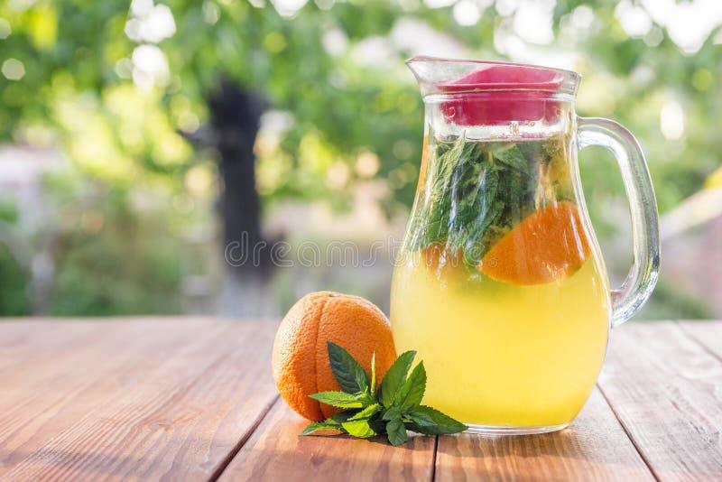 Lemonadkanna med apelsinen, mintkaramellen och is på trädgårdtabellen Hemlagad orange lemonad med mintkaramellen arkivfoton