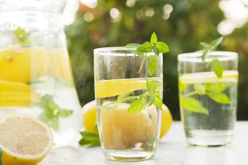 Lemonadnärbilden på en konkret bakgrund med citroner klippte öppet Hela citroner, mintkaramell, ny sommarlemonad i naturen, begre arkivfoto