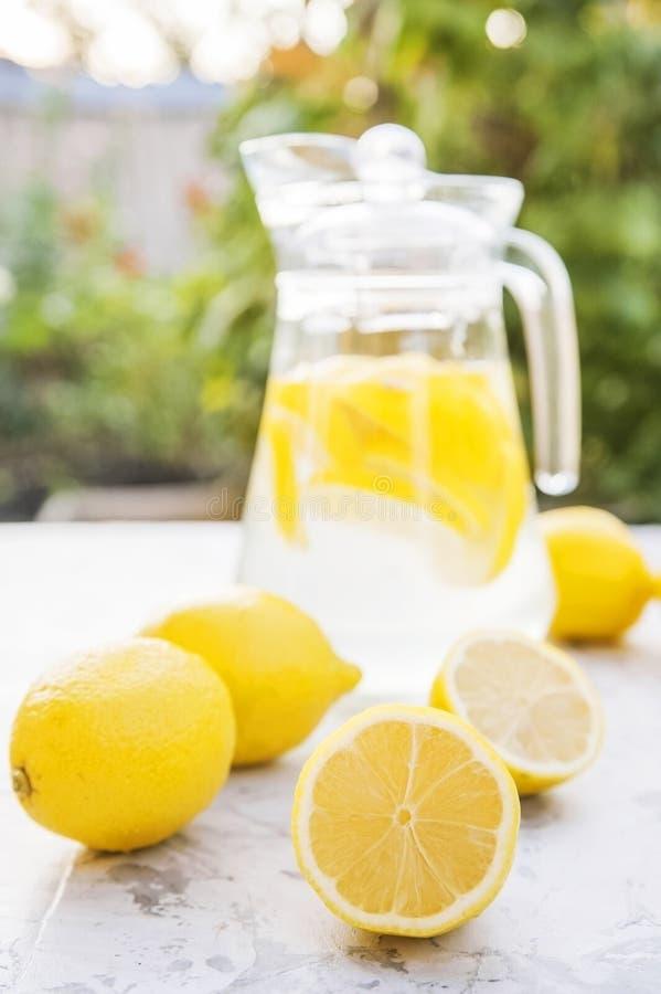 Lemonadnärbilden på en konkret bakgrund med citroner klippte öppet Hela citroner, mintkaramell, ny sommarlemonad i naturen, begre arkivbilder